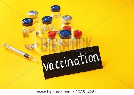 Card with word VACCINATION, ampules and syringe on color background