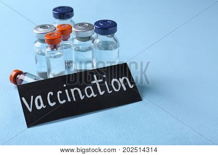 Card with word VACCINATION and ampules on color background