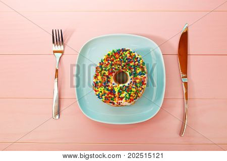 Donut dish and silverware on a pastel blue and pink background