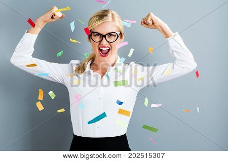 Young strong business woman celebrating with confetti