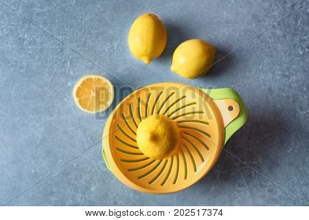 Composition with lemons and plastic squeezer on grey background