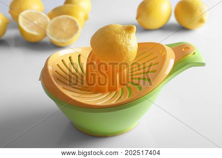 Composition with plastic squeezer and cut lemons on white background