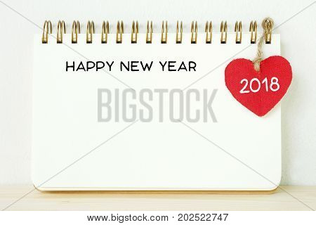 Red fabric heart shape with 2018 word and happy new year on blank note book paper new year template