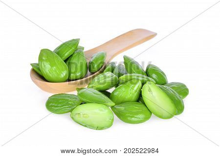 pile of sato parkia speciosa seeds or bitter bean in wooden spoon isolated on white background