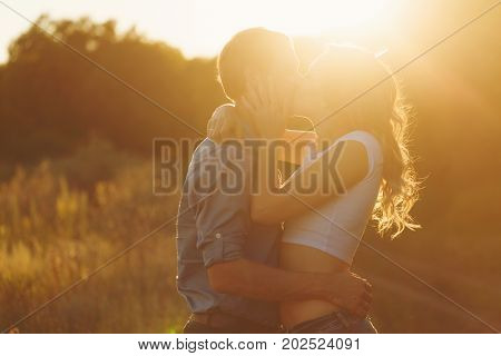 Loving couple at sunset. Guy hugs girl. They passionately kiss. Love and romance. Young and happy.