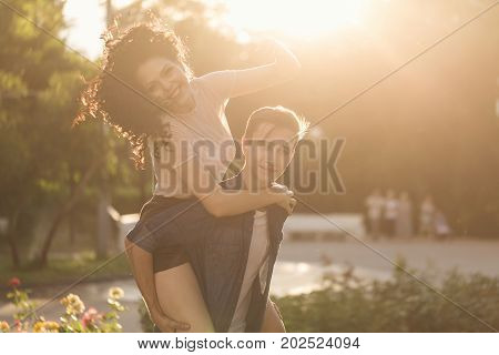Teenagers are walking in the city park. He rolls her on the shoulders of piggyback. She is in love. Couple in love. Romantic first date. Carefree youth.