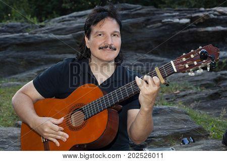 Hispanic man playing guitar outdoors in park.
