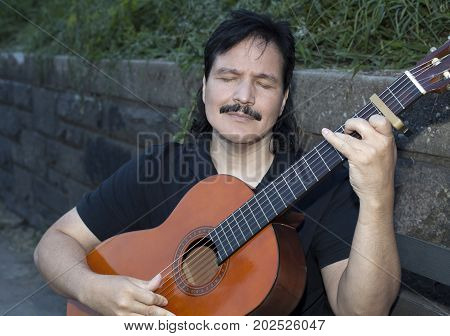 Hispanic man sitting on park bench playing acoustic guitar with passion.