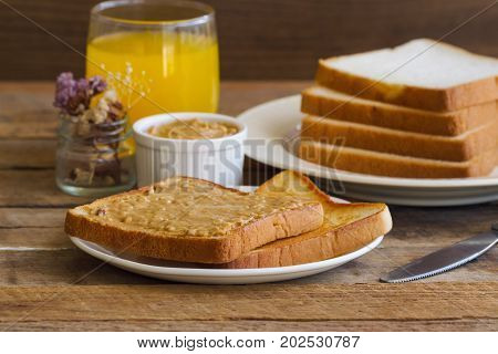 Toast bread with homemade peanut butter served with orange juice. Homemade toast bread with peanut butter on wood table for breakfast.Delicious toast bread with homemade peanut butter ready to served. Toast bread spread with peanut butter.