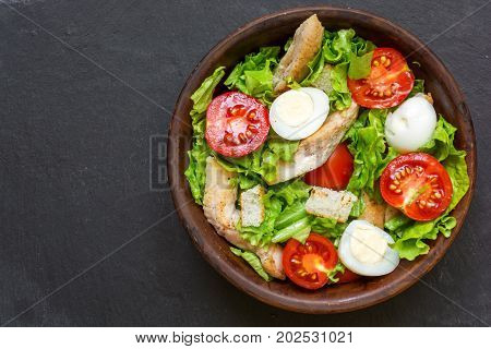 Caesar salad with croutons quail eggs cherry tomatoes and grilled chicken in a bowl on dark stone background. top view