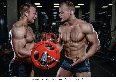 Handsome young muscular Caucasian man of model appearance working out training arms in gym gaining weight pumping up muscles bicep and tricep with dumbbells and on machines gaining weight and poses