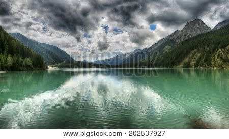 Lake of Anterselva surrounded by mountains with blue sky and dark clouds in the background on a summer day Sud Tirol Italy