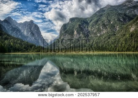 Lake of Toblach surrounded by mountains with blue sky and clouds in the background on a summer day Sud Tirol Italy