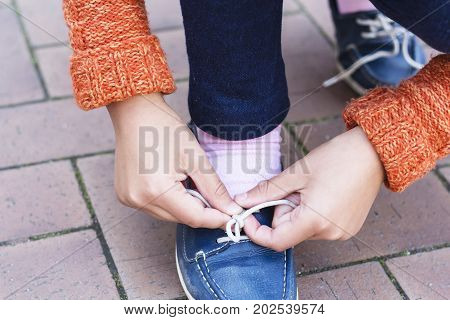 Closeup of a teenage girl hands tying shoelaces. The concept of travelling, walking and adventure.