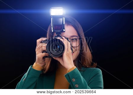 Female photographer using flash to take photos in darkness