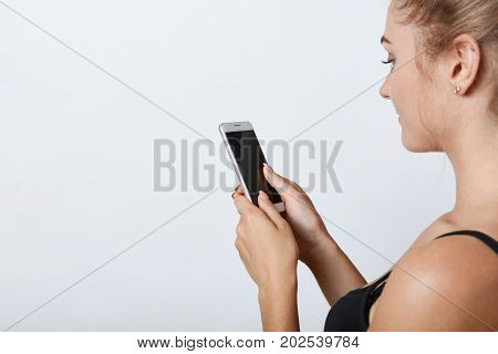Sideways Portrait Of Female With Healthy Pure Skin Holding Mobile Phone In Hands With Blank Screen,