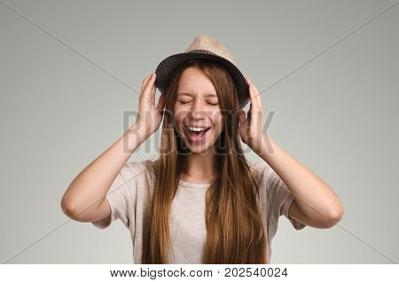 Positive Casual Woman Posing. Emotional Girl Portrait. Young Female With Hat. The Model With Closed