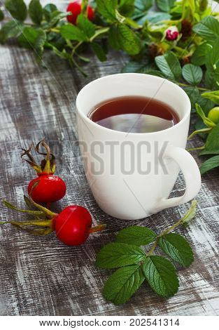 Tea from a dogrose in a mug on a wooden background with fruits.