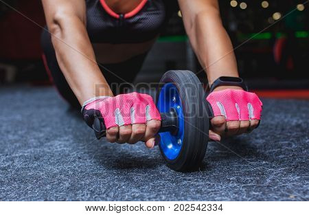 Slim bodybuilder girl does the exercises with roller for press in the gym. Sports concept fat burning and a healthy lifestyle.