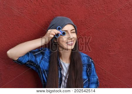 hipster girl holding fidget spinner. Funny portrait of young woman with spinner. Popular trendy stress relieving toy