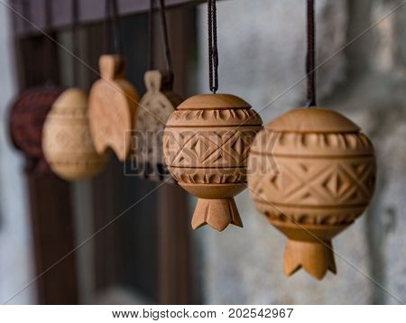 Intricate carved wooden decorations hang in shop in Dilijan Armenia