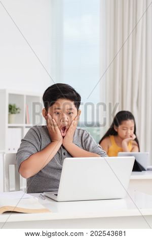Shocked Vietnamese boy looking at laptop screen with test