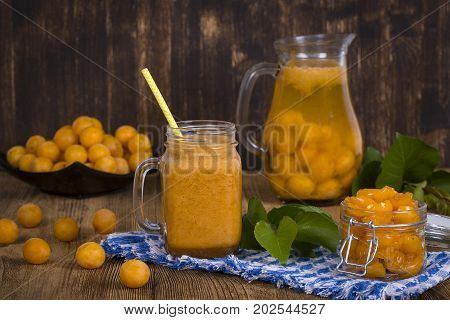 Healthy eating food dieting and vegetarian concept - mug glass of juice smoothie shake from yellow plum lemonade jam and ripe yellow plum on wooden table. Bio healthy food and drink. Organic diet