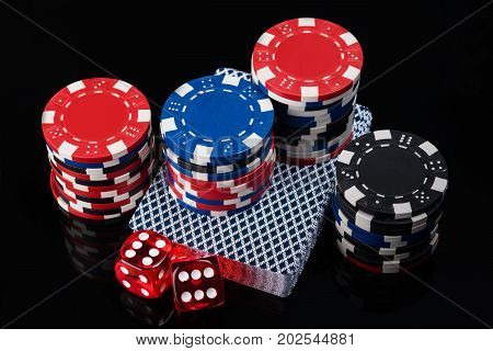 beautiful dice set cards and poker chips on a black background