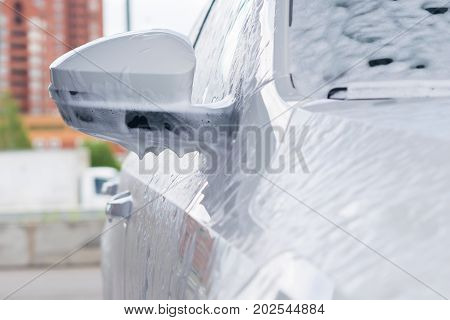 side mirror on a white car in a non-contact foam on the sink