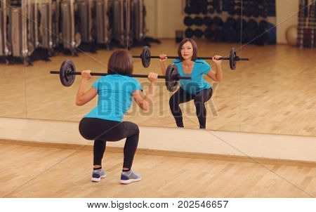 Bodybuilding. Woman Exercising With Barbell In Fitness Class. Female Workout In Gym Doing Squats Wit