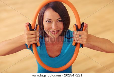 Magic Pilates Ring Woman Aerobics Sport Gym Exercises On The Floor, Smiling And Looking To Camera