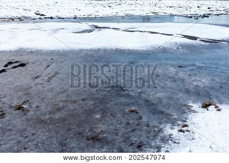 Ground With Winter Ice Melting, And Water Bubbles In The Mud And Grass, Organic Abstract Ground Text