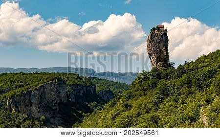 Katskhi Pillar is a single 120 foot tall towering pillar of rock with a small cell for a single monk at the top