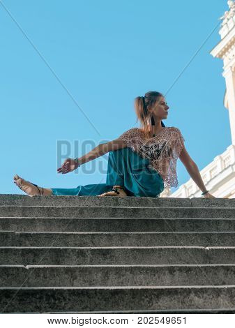 Woman with meditation on top of stair in city background. Young girl in alladin pants doing yoga in the city.