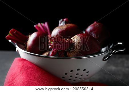 Collander with delicious ripe beets on table