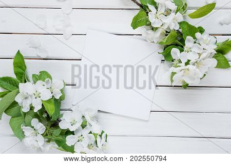 Scrapbook page of wedding or family photo album with copy-space frame with white flowers and green leaves on light wooden background; top view flat lay overhead view. Mocap