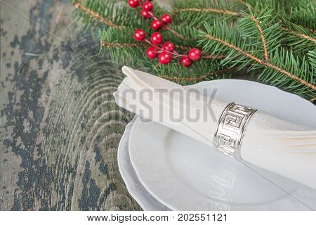 White linen napkin silver napkin ring are on the white dinner plate as well as red holly berries and green spruce branches which is located on a old wooden table with space for text