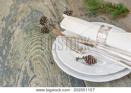Christmas table: silver knife fork and linen napkin lie on the white dinner plate as well as green spruce branch and cones which is located on a old wooden table with space for text