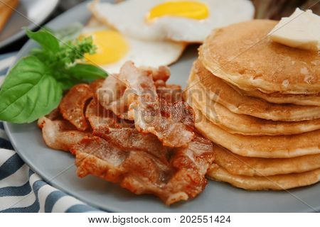 Tasty breakfast with fried eggs, pancakes and bacon on plate