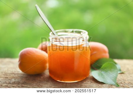 Apricot jam in jar with spoon on green background