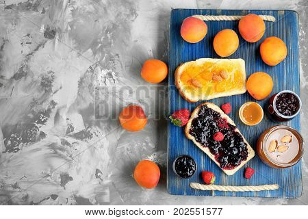 Two slices of bread with apricot and berry jams on wooden tray