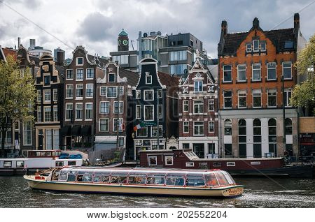 Amsterdam Netherlands - 27 April 2017: Cruise tourist boat against Houseboats living barges and typical curves dutch houses with large windows in Binnenamstel canal in Amsterdam at sunset.