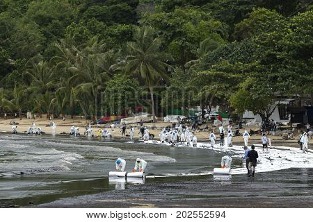 Rayong Thailand - July 31 2013: Workers roll out a ream of absorbent paper for clean-up crude oil spilled at Ao Prao Beach on July 31 2013 in Koh Samet Rayong Thailand.