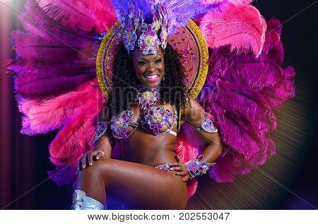 MOSCOW RUSSIA- JANUARY 2017: Beautiful bright colorful carnival costume illuminated stage background. Samba dancer hips carnival costume bikini feathers rhinestones close up