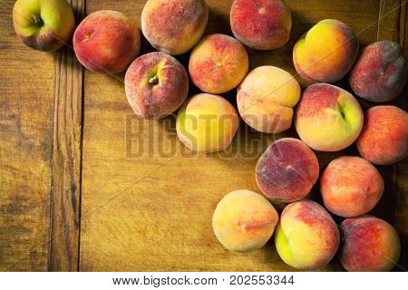 Many silky peaches on wooden table, top view. Fresh ripe summer fruit on kitchen table