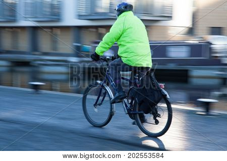 Person riding a bicycle along a canal with helmet and high visibility jacket