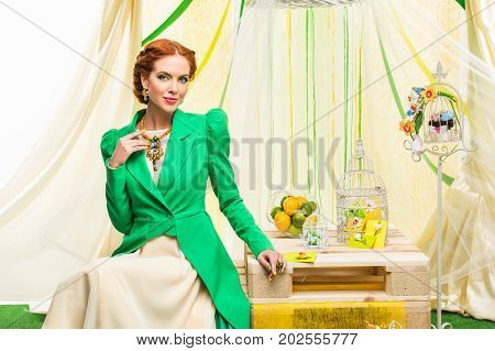 beautiful young woman with red hair in yellow dress and green jacket sitting at wedding present table. studio shot. copy space.