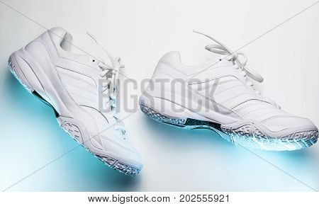 Leather sports sneakers on white background with blue backlight
