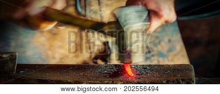A Wisconsin blacksmith practicing his craft on a stick of iron.
