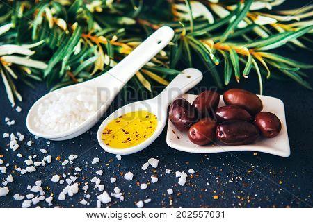 Greek olives sea salt spices olive oil with olive tree leaves on a black background